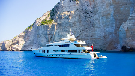 Luxury white yacht navigates into beautiful blue water near Zaky. View from the top of a large white yacht at Navagio Beach. Stockfoto