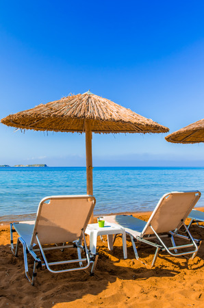 sunbeds: Straw umbrellas and sunbeds on a red sand beach and turquoise water. Parasols and tanning beds on the beach. Stock Photo