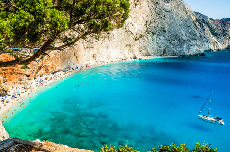 greece shoreline: Porto Katsiki beach in Lefkada island, Greece. Beautiful view over the beach. The water is turquoise and there are tourists on the beach and a boat on the sea.