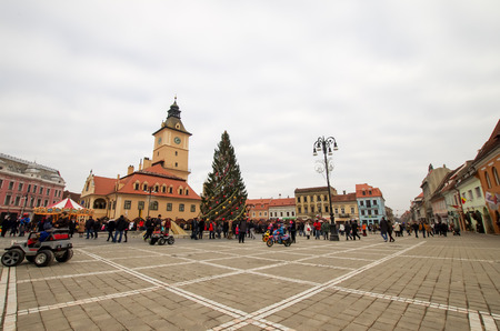 huge christmas tree: Brasov, Romania - December 26, 2015: The Old Town Hall. Winter scene with a huge Christmas tree in the central square, Piata Sfatului.