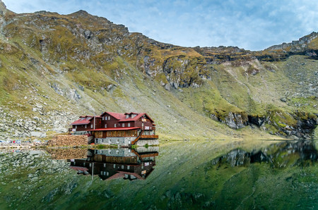balea: BALEA LAKE, ROMANIA - SEPTEMBER 19, 2015: Beautiful view of Balea Lake cottage on Fagaras Mountains, Carpathian, Romania. The image of the chalet is reflected in the lake.