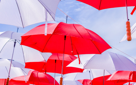 withe: Hanging Multicolored umbrellas over blue sky. Red and withe large size umbrellas onto the blue sky.