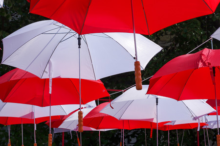 large size: Hanging Multicolored umbrellas over blue sky. Red and withe large size umbrellas onto the blue sky.