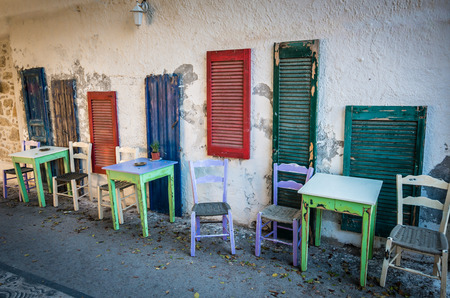 kreta: Old tables and seats on street. Green and white tables and white and purple seats near blue, green and red windows on a street in Crete island, Greece. Stock Photo