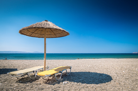 Straw umbrella on a sandy beach in Greece. Beach chairs with umbrellas on a beautiful beach in Crete island.