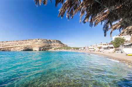 kreta: Matala beach on Crete island, Greece. Tourists relax and bath in crystal clear water of Matala in south of Creta. There are many caves near the beach.
