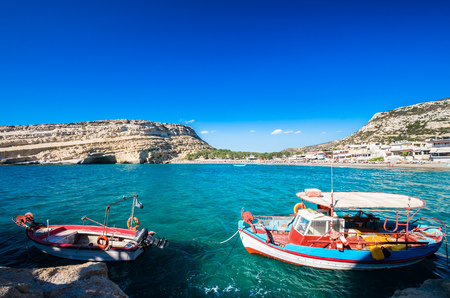 kreta: Matala beach on Crete island, Greece. There are two boats in the foreground and many caves near the beach.
