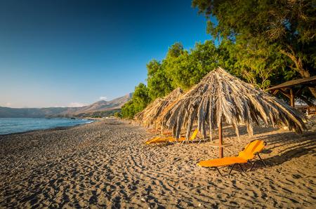 sunbeds: Sfinari Beach in Crete island, Greece. Straw parasols and sunbeds on the beach in twilight.