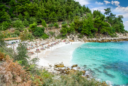 Marble beach (Saliara beach), Thassos Islands, Greece. The most beautiful white beach in Greece. Tourists enjoying a nice day at the beach. Straw umbrellas (straw parasol) and sunbeds on the beach. Zdjęcie Seryjne - 64493718