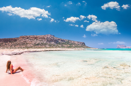 kreta: Balos lagoon on Crete island, Greece. A girl on a beach with pink sand.