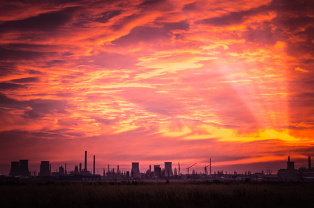 Spectacular sunset with clouds in the sky. Beautiful sunset over a oil refinery. Stock Photo