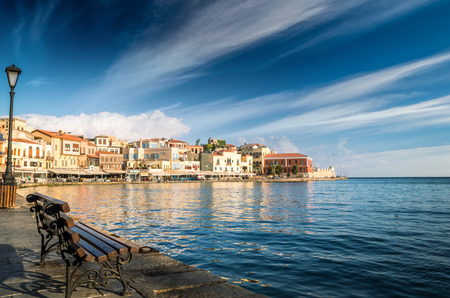 CHANIA, CRETE - JUNE 26, 2016: View of the old venetian port of Chania on Crete island, Greece. Tourists relaxing on promenade.