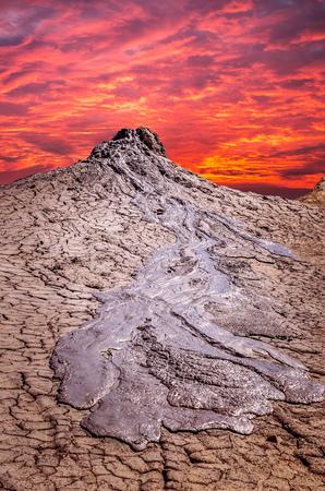 erupting: Sunset over muddy volcanoes, Buzau county, Romania. Active mud volcanoes landscape in Europe.