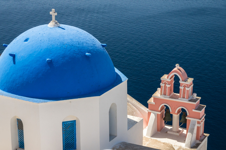 Oia Village, Santorini Cyclade islands, Greece. Beautiful view of a blue dome church and a pink tower-bell.