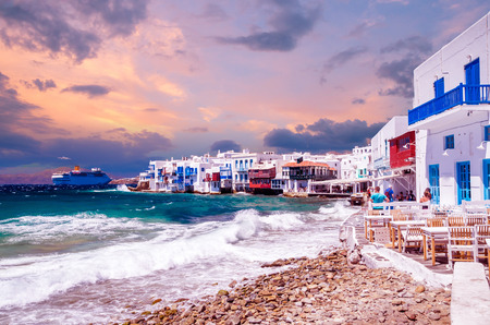 Little Venice, Mykonos island, Greece. Colorful buildings and balconies near the sea and a large white cruise ship.