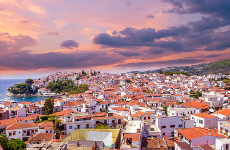 Sunset over Skiathos town on Skiatos Island, Greece. Beautiful view of the old town with boats in the harbour. Banco de Imagens