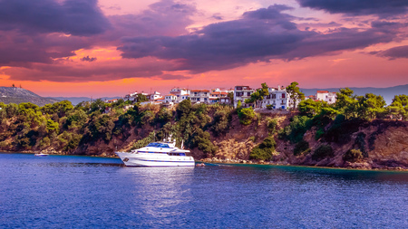 Sunset over Skiathos town, Greece. Luxury yacht in the bay of Skiathos, near the harbour