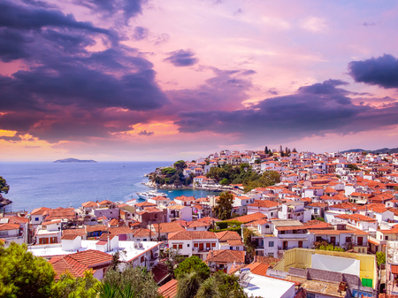 Sunset over Skiathos town on Skiathos Island, Greece. Beautiful view of the old town with boats in the harbor.