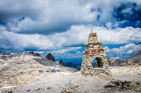 Sella massif, Dolomites mountains, Italian Alps. Cairn on the stone in the foreground and rifugio Boe in the second plane. Hiking to Piz Boe