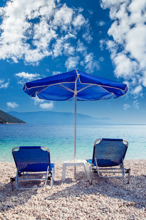 Blue umbrella and tanning beds on the beach. Parasols and sunbeds on a beautiful beach in Greece.