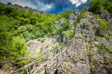 Emen Canyon, Bulgaria. Wood bridge over the river into a luxuriant forest Reklamní fotografie - 126304403