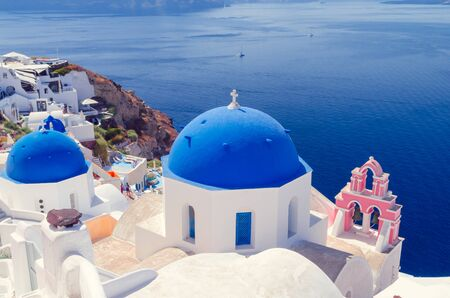 Oia Village, Santorini Cyclade islands, Greece. Beautiful view of a blue dome church and a pink towerbell.