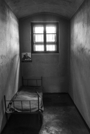 illegal act: Dark prison cell with a bed and window Stock Photo