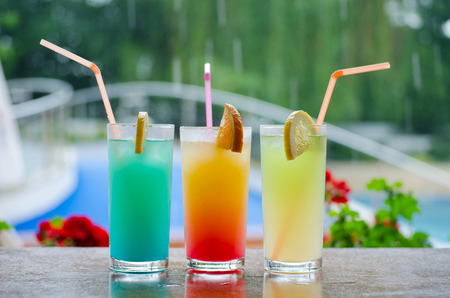 Three colorful cocktails sitting on the table around the pool