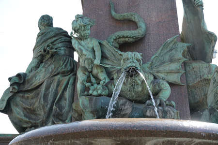 A detail of a fountain with a winged and tailed dragon spitting water and a cherub observing. They bare both of greenish color due to patina. 報道画像
