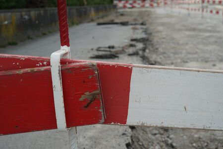 Two construction barrier planks of red and white close-up fixed together on a civil engineering construction site with dismantled road to give place to new transport project