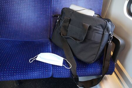 New equipment of a commuter in coronavirus COVID-19 times, a N95 face mask to prevent spreading of an infection. Measures during and after lockdown.