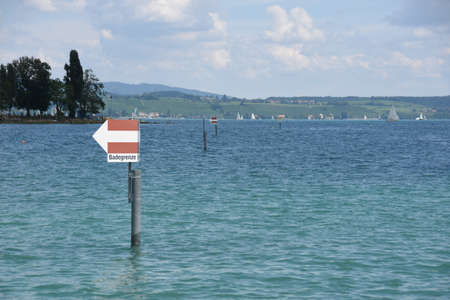 Sign for swimming border on the pole in the Lake Constance, Bodensee, on the river Rhine at the northern foot of the Alps near city Konstanz. Water is azure blue and sky is covered with heap clouds Stock fotó