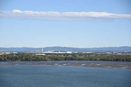 Approach to Port of Brisbane which is located in the lower reaches of the Brisbane River during ebb low tide. View from merchant cargo container vessel, air traffic controller and airport.