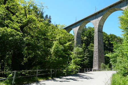 Sitterviaduct railway bridge in lateral view and upward perspective. The bridge is on a St. Gallen hiking trail in Eastern Switzerland surrounded by mixed forests.