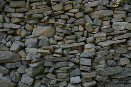 A wall consisting of layered flat stones creating a structure suitable as a background.