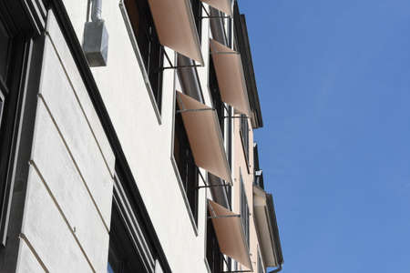 Facade of an old residential building in the center of Zurich, Switzerland. The building is redecorated with textile unblinds or awnings giving it mediterranean and positive atmosphere of gentrification.