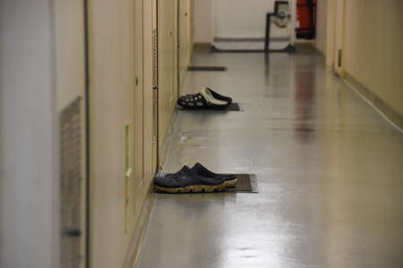 Neatly lying or laid protective slippers in waxing alleyway in front of cabins of ship crew inside superstructure of container vessel Stock Photo
