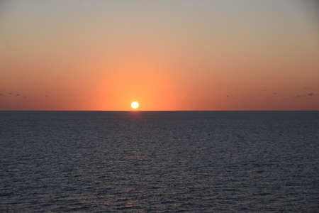 Sunset in Atlantic ocean. The sky is displayed in varies harmonic shades of red, orange and yellow during calm weather in spring time.