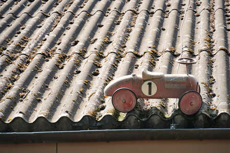 An red swing car placed on an old gray corrugate fibre cement roof covered with moss. The car is old fashioned and has number 1 painted on it. Stock fotó