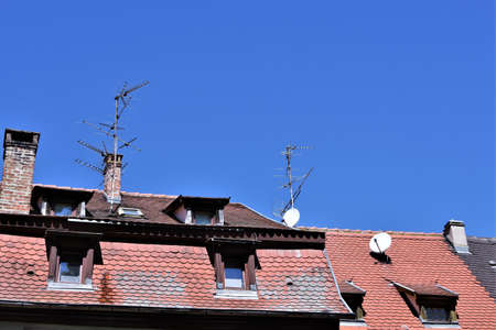 Red and brown tile cladding roof with dormer windows or roof windows, parabolas and old fashion analog TV antennas in Colmar, France under blue sky during summer day.