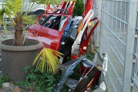 Removed and scrapped various colored car doors leaned against metal meshed wire fence in industrial factory yard in Dietikon, Switzerland. On the left side is plastic flower pot with palm tree.