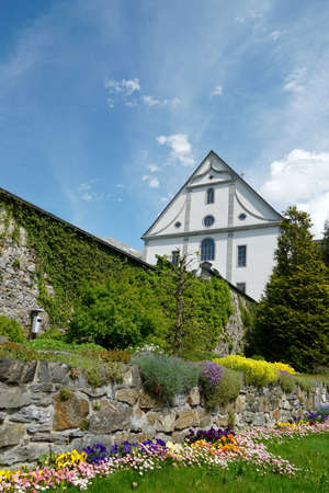 Facade of the church belonging to monastery and a wall surrounding the terrain of the monastery in Engelberg, Switzerland. The wall is covered by decorative vegetation.