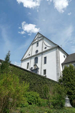 Facade of church belonging to monastery from behind in Engelberg, Switzerland. The wall, covered with plants, surrounding terrain of the monastery.