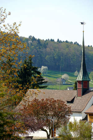 Old reformed church building with copper and tile cladding roof in Urdorf, Switzerland among trees, lateral view with village shield on the top of he tower with woods on the background Stock fotó