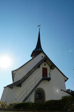 Old reformed church building in Urdorf, lateral view on a clear day with blue sky, the photo taken in upward perspective.