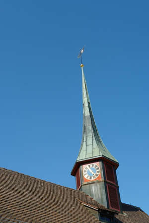 Old reformed church building with copper and tile cladding roof in Urdorf, Switzerland in lateral view with village shield on the top of the tower with blue sky on background Imagens
