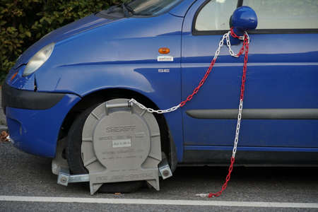 Wheel clamp installed on a wheel of an incorrectly parked car. A chain in red and white is attached to the clamp and the other end to the side mirror of the car.