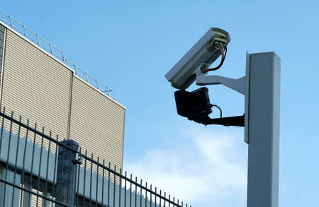 CCTV security camera on a post to watch factory yard of private company for security reasons with blue sky as background. In general serves as a symbol for control, observation spying and protection.