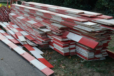 Wooden red and white barrier planks on a building or construction site of civil engineering stored on stack ready for use.