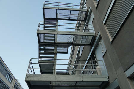 Exterior metal stairs, fire escape route, attached to outside of modern industrial and administrative brick building in Dietikon, Switzerland. Stock fotó